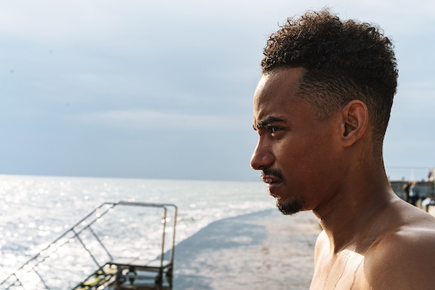 ビーチの海で屋外のハンサムな若いアフリカのスポーツ選手の画像。