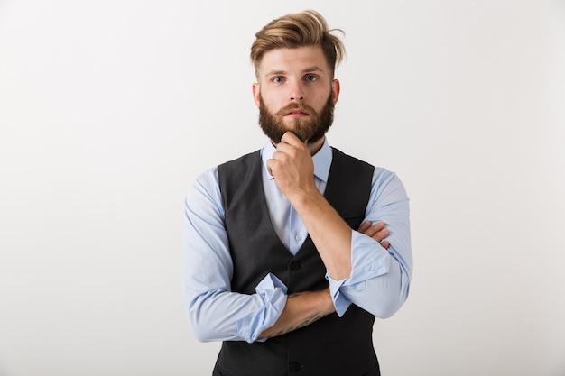 Изображение красивого молодого бородатого человека, стоящего изолированно на белом фоне стены.