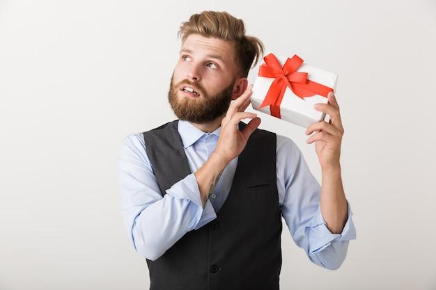 Изображение красивого молодого бородатого человека, стоящего изолированно над белой стеной, держащей подарочную коробку.