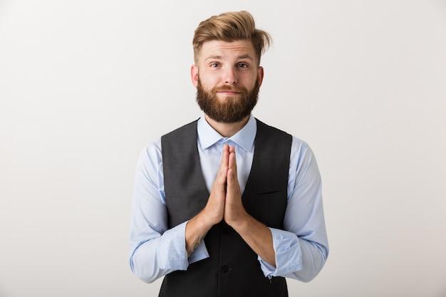 Изображение красивого молодого бородатого мужчины, стоящего изолированно над белой стеной, делает обнадеживающий жест пожалуйста.