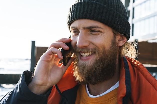 Изображение красивого молодого рыбака в пальто и шляпе на берегу моря, говорящего по телефону.