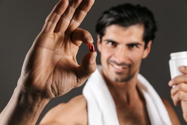 Изображение красивого молодого человека изолированного при полотенце держа витамины пилюлек.