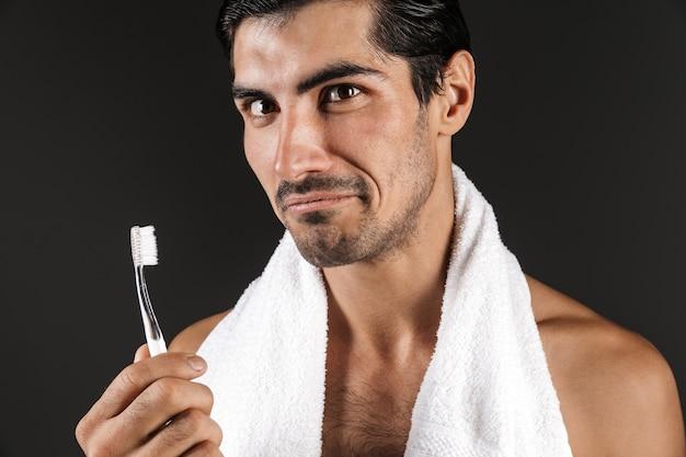 그의 이빨을 청소하는 고립 된 칫 솔 질 포즈 잘 생긴 젊은 남자의 이미지.