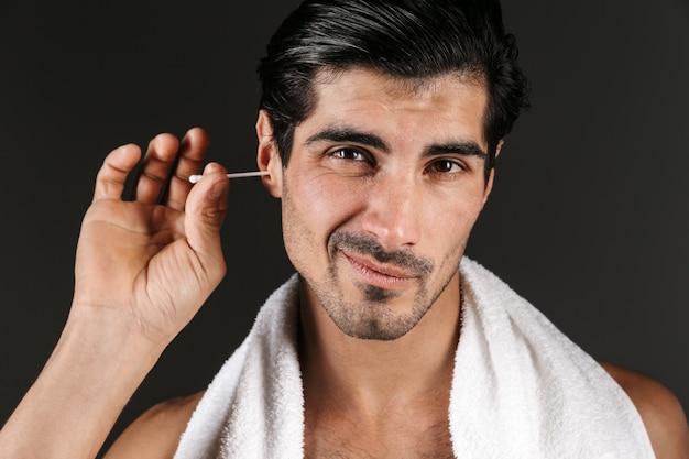 彼の耳を掃除する孤立したポーズをとっているハンサムな若い男の画像。