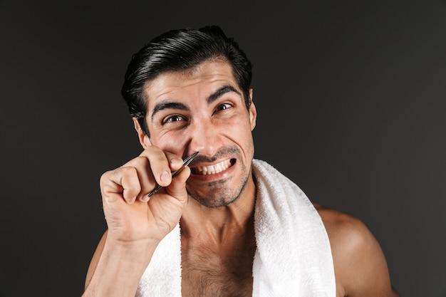 핀셋으로 코에서 고립 된 제모 머리를 포즈 잘 생긴 젊은 남자의 이미지.