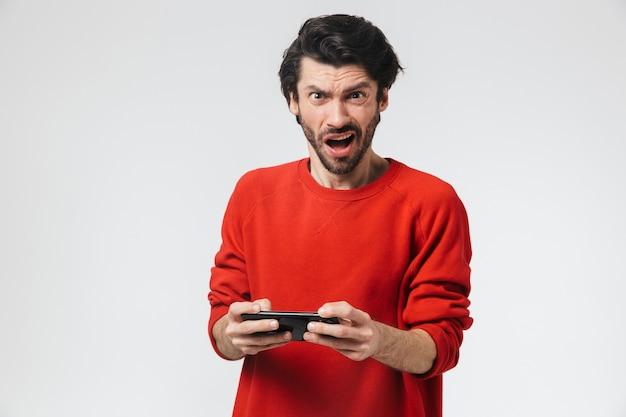Изображение красивого молодого нервного возбужденного человека, позирующего над белой стеной, играть в игры по мобильному телефону.