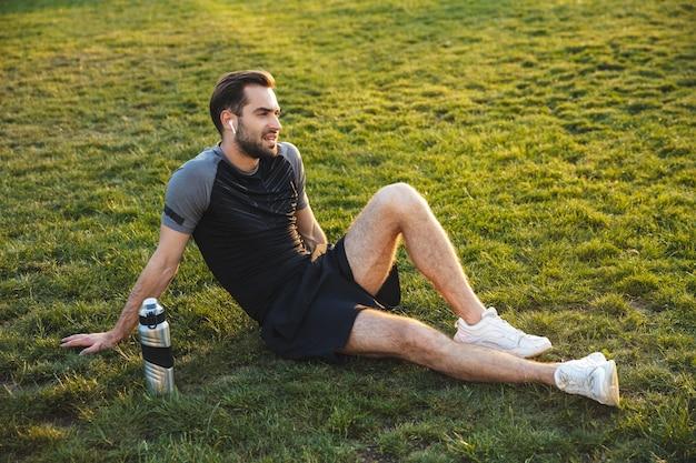 イヤホンで音楽を聴いて座って休んでいる自然公園の場所で屋外でポーズをとっているハンサムな若い強いスポーツの男性の画像。