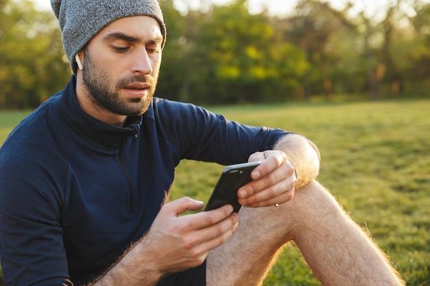 電話を使用してイヤホンで音楽を聴いて座って休んでいる自然公園の場所で屋外でポーズをとって帽子をかぶっているハンサムな若い強いスポーツの男性の画像。