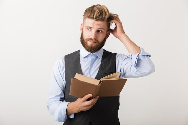 Изображение красивого молодого мышления бородатого человека, стоящего изолированно над белой стеной, читая книгу.