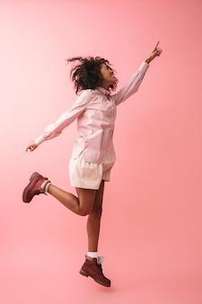 Изображение счастливой красивой молодой африканской женщины, позирующей изолированное прыгающее указание.