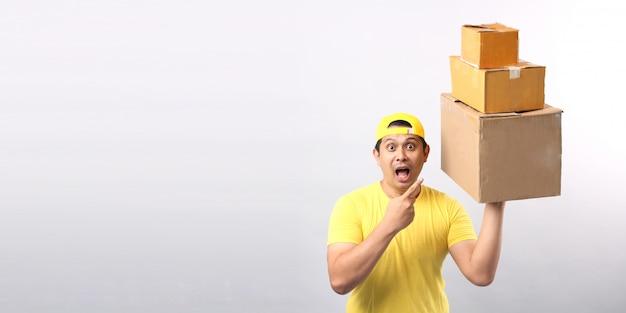 白い壁に分離された小包郵便ポストで立っている黄色い帽子で幸せな配達アジア人のイメージ