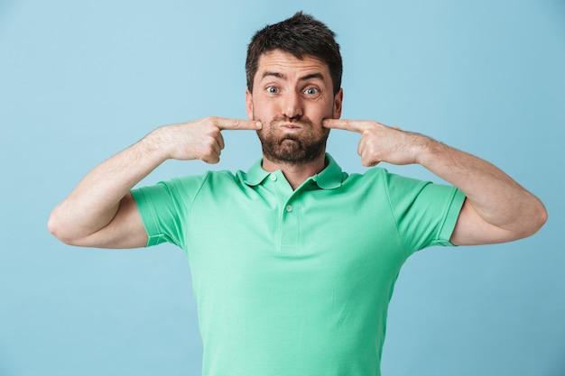 Изображение счастливого забавного молодого красивого бородатого мужчины, позирующего изолированно над голубой стеной.