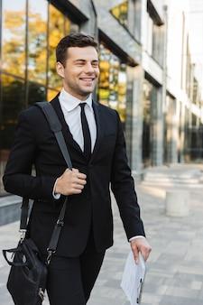 Изображение счастливого красивого молодого бизнесмена, прогулки на открытом воздухе возле бизнес-центра с буфером обмена.