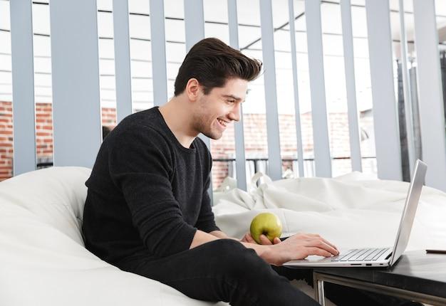 Изображение счастливого красивого молодого человека дома в помещении с помощью портативного компьютера ест яблоко.