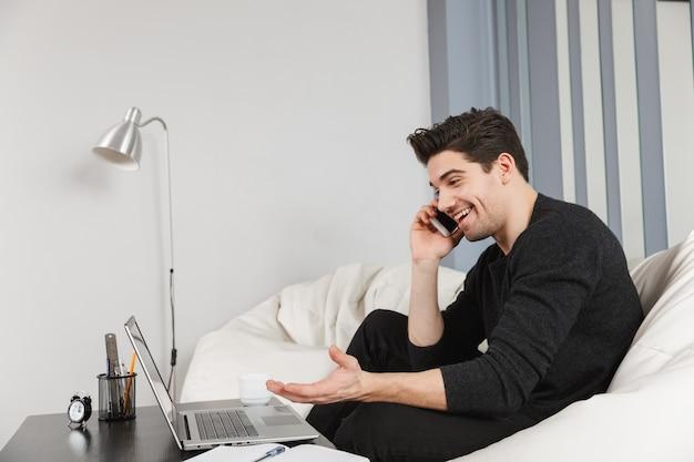 Изображение счастливого красивого молодого человека дома в помещении с помощью портативного компьютера, разговаривает по мобильному телефону.