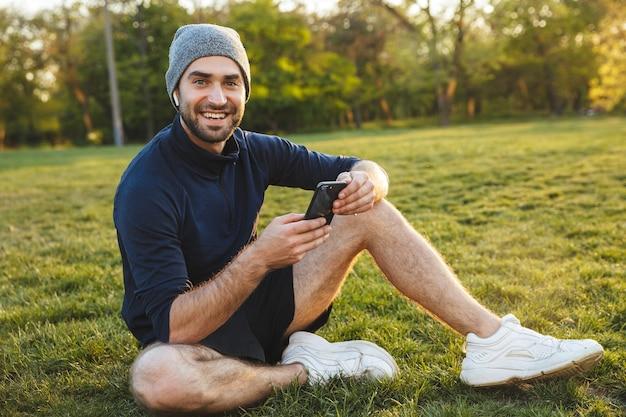 携帯電話を使用してイヤホンで音楽を聴いて座って休んでいる自然公園の場所で屋外でポーズをとって帽子をかぶって幸せなハンサムな若い強いスポーツの男性の画像。