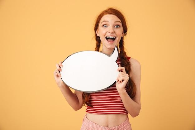 Изображение счастливой потрясенной молодой красивой рыжей женщины, позирующей изолированной над желтой стеной, держащей речевой пузырь.