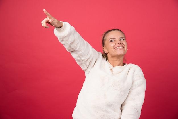Изображение счастливой женщины, указывая пальцем в сторону