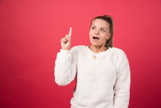 指を上に向けて幸せな女性の画像 無料写真