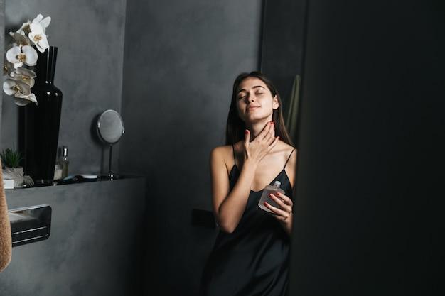 Изображение счастливой молодой красивой женщины в ванной заботится о ее коже.