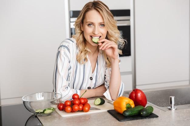 家庭料理のキッチンでポーズをとって幸せな若い美しい女性の画像。