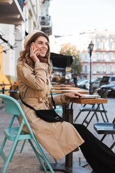 휴대 전화로 이야기하는 카페에 앉아 노트북 컴퓨터를 사용 하여 야외에서 걷는 행복 한 젊은 아름 다운 여자의 이미지.