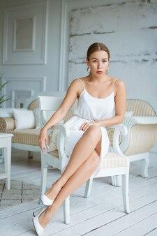 흰색 안락의자에 앉아 포즈를 취하는 하얀 드레스를 입은 행복한 젊은 비즈니스 여성의 이미지...