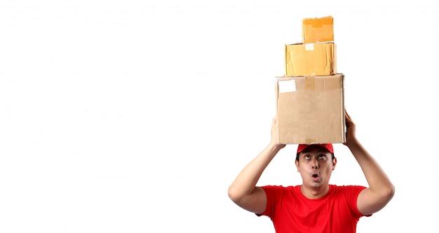 白い壁に分離された小包郵便箱で赤い帽子立っている幸せな若い配達アジア人のイメージ
