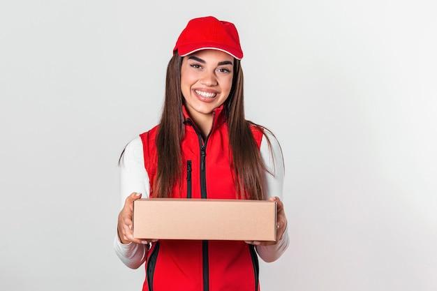 白い背景の上に分離された小包の郵便ポストと立っている赤い帽子で幸せな若い出産女性の画像。