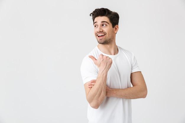 Изображение счастливого молодого возбужденного эмоционального человека, позирующего изолированным над белой стеной. глядя в сторону указывая.