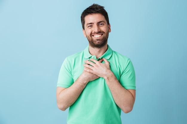 Изображение счастливого молодого красивого бородатого мужчины, позирующего изолированно над голубой стеной.