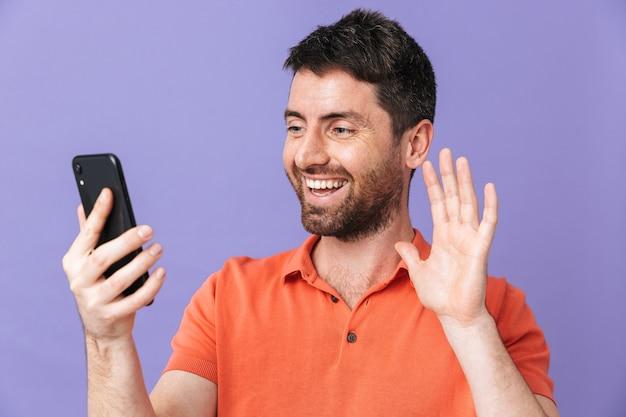 Изображение счастливого молодого красивого бородатого мужчины, позирующего изолированно над фиолетовой фиолетовой стеной, говорящей размахиванием мобильного телефона.