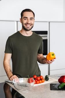 自宅のキッチンで料理をしている幸せな若いハンサムな男の画像は、朝食を持っています。