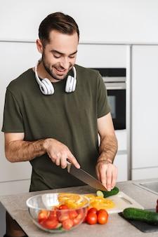 ヘッドフォンで音楽を聴いて自宅のキッチンでポーズをとって幸せな若いハンサムな男の画像。