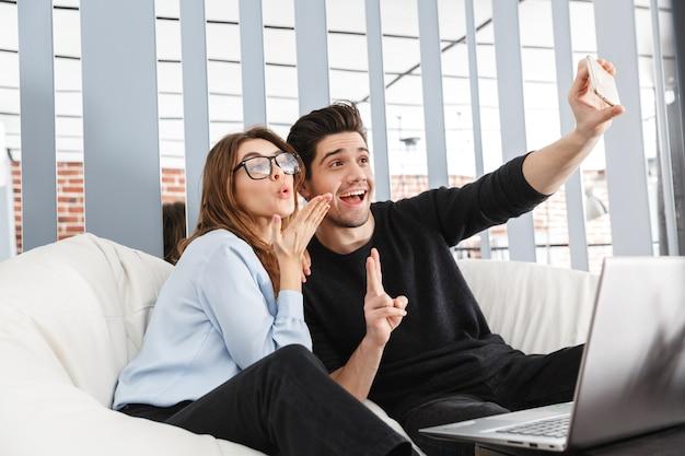 Изображение счастливой молодой влюбленной пары дома в помещении с помощью портативного компьютера сделать селфи по телефону.