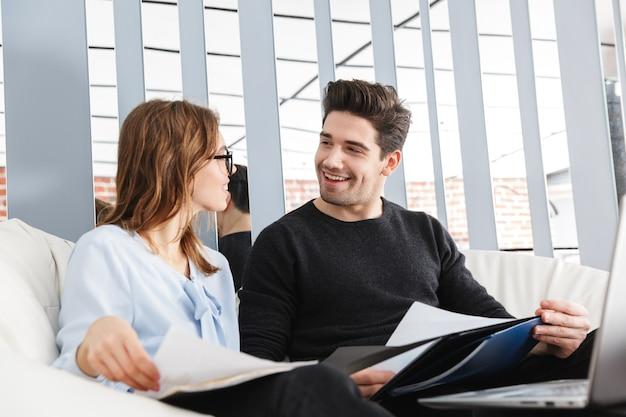 Изображение счастливой молодой любящей пары дома в помещении с помощью портативного компьютера работы с документами.