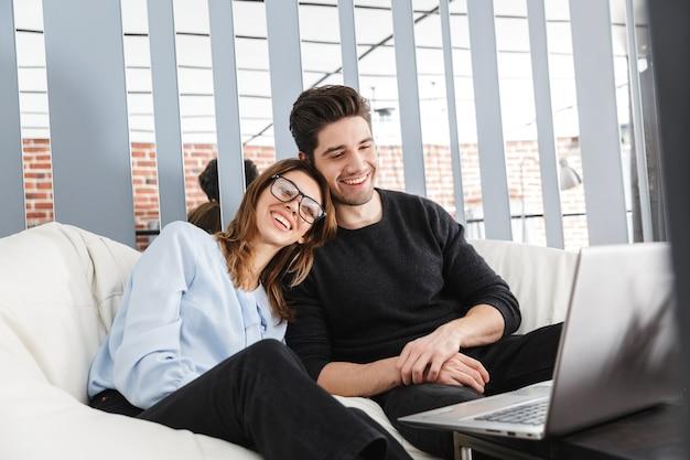 Изображение счастливой молодой любящей пары дома в помещении с помощью портативного компьютера.