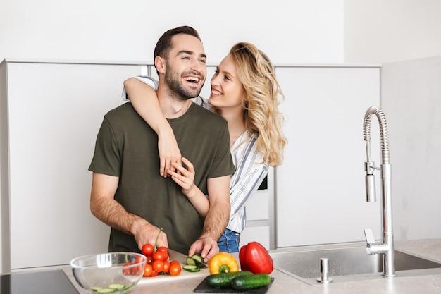 家庭料理のキッチンでポーズをとっている幸せな若い愛情のあるカップルの画像は、朝食を抱き締めています。