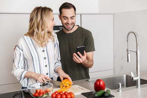 家庭料理のキッチンでポーズをとっている幸せな若い愛情のあるカップルの画像は、携帯電話を使用して朝食をとります。