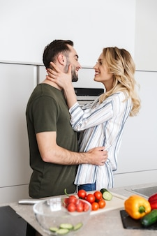キスを抱き締めて自宅のキッチンでポーズをとって幸せな若い愛情のあるカップルの画像。
