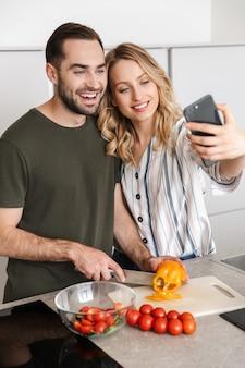Изображение счастливой молодой любящей пары, позирующей на кухне дома, обнимая, делает селфи по мобильному телефону.