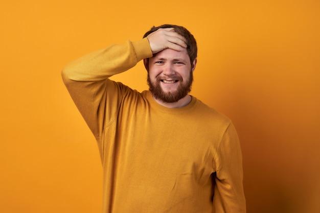 基本的な服を着た男の画像、手で髪を保持しているひげを持つ不幸なハンサムな男のクローズアップ。