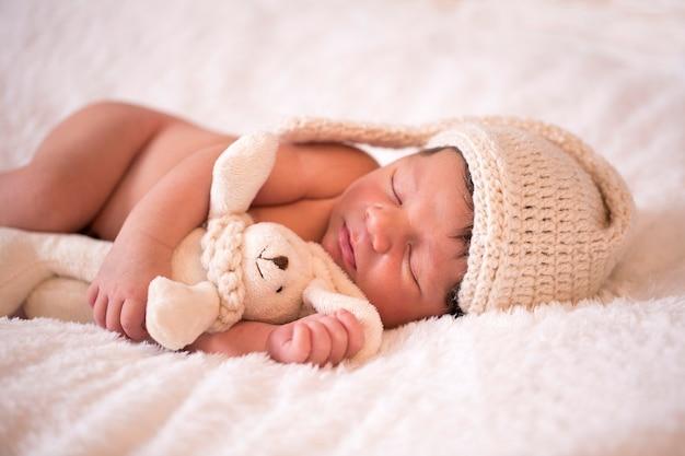 Изображение новорожденного бразильского ребенка, свернувшегося в клубок, спит в одеяле