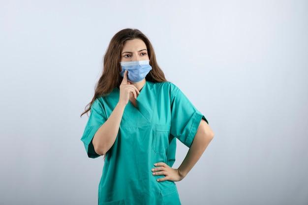 멀리 보이는 녹색 유니폼에 잠겨있는 아름다운 간호사의 이미지