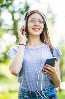 헤드폰으로 아름 다운 녹색 공원 듣는 음악에 야외에서 앉아 기쁘게 행복 젊은 십 대 소녀 학생의 이미지.