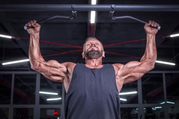 ジムで懸垂をしている強力なアスリートの画像。バックポンピング。フィットネスとボディービルのコンセプト。ミクストメディア