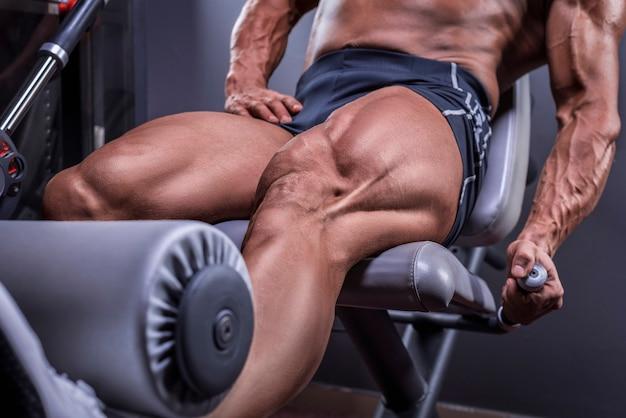 ジムで大腿四頭筋運動をしている強力なアスリートの画像。フィットネスとボディービルのコンセプト。ミクストメディア