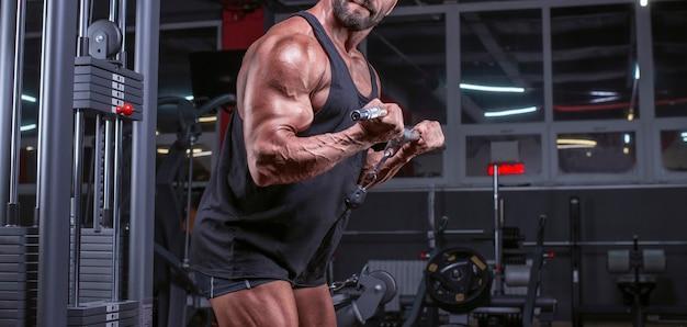 ジムのクロスオーバーで運動している強力なアスリートの画像。上腕二頭筋のポンピング。フィットネスとボディービルのコンセプト。ミクストメディア
