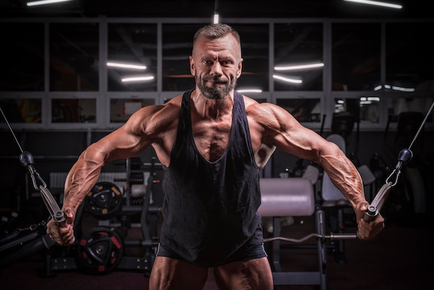 ジムのクロスオーバーで運動している強力なアスリートの画像。フィットネスとボディービルのコンセプト。ミクストメディア