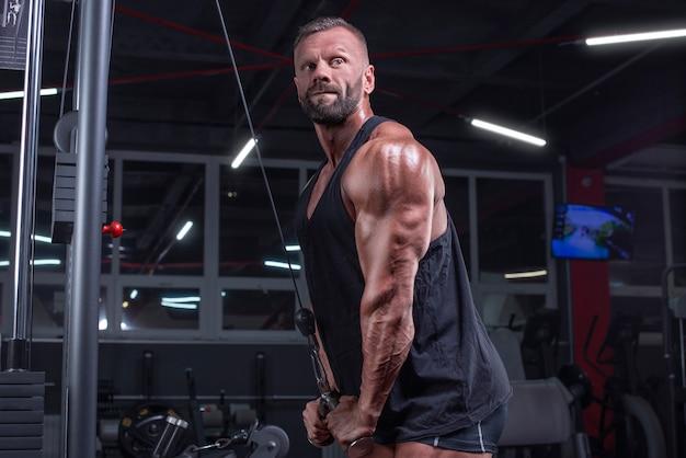 ジムのクロスオーバーで運動している強力なアスリートの画像。上腕三頭筋のポンピング。フィットネスとボディービルのコンセプト。ミクストメディア